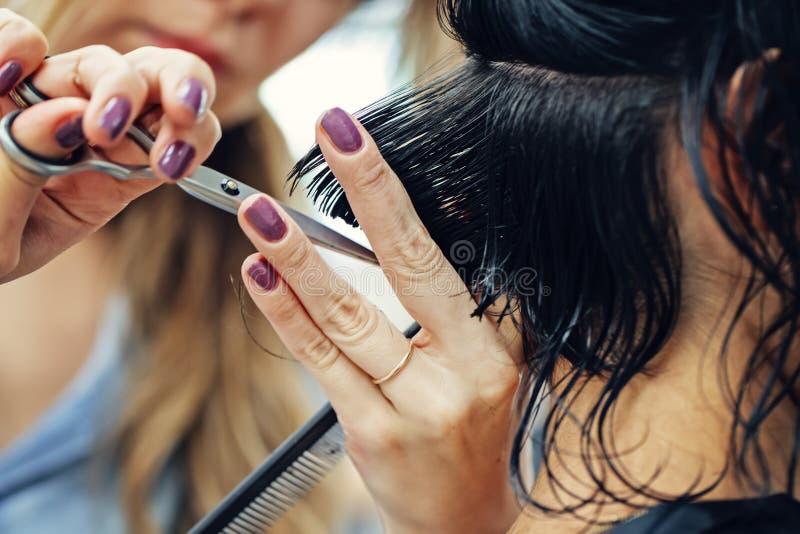 Imagem macro do tiro do close up do cabelo da mulher do cliente do corte do cabeleireiro do barbeiro no salão de beleza imagem de stock