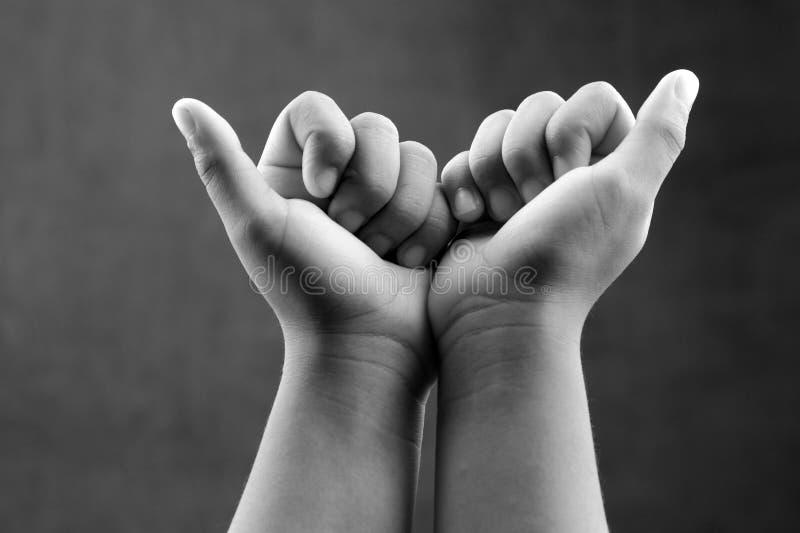Imagem monocromática das mãos fechados de uma criança para conceitos da força e da unidade foto de stock