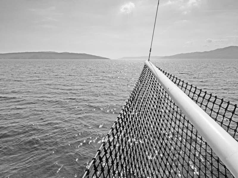Imagem monocromática de ilhas croatas no mar de adriático com uma curva do ` s do navio no primeiro plano fotografia de stock royalty free