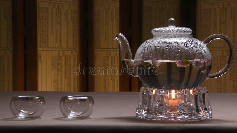 Imagem morna bonita da chaleira transparente do bule com chá preto verde saboroso em uma tabela com velas Chaleira de vidro imagem de stock royalty free