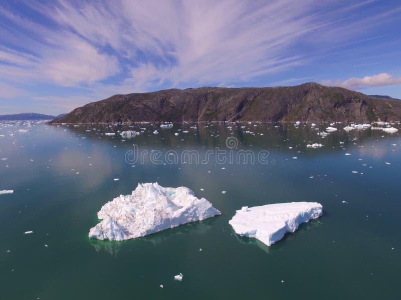 Imagem oblíqua do zangão com os dois grandes iceberg no primeiro plano e as montanhas e o gelo e as nuvens altas, wispy no fundo foto de stock