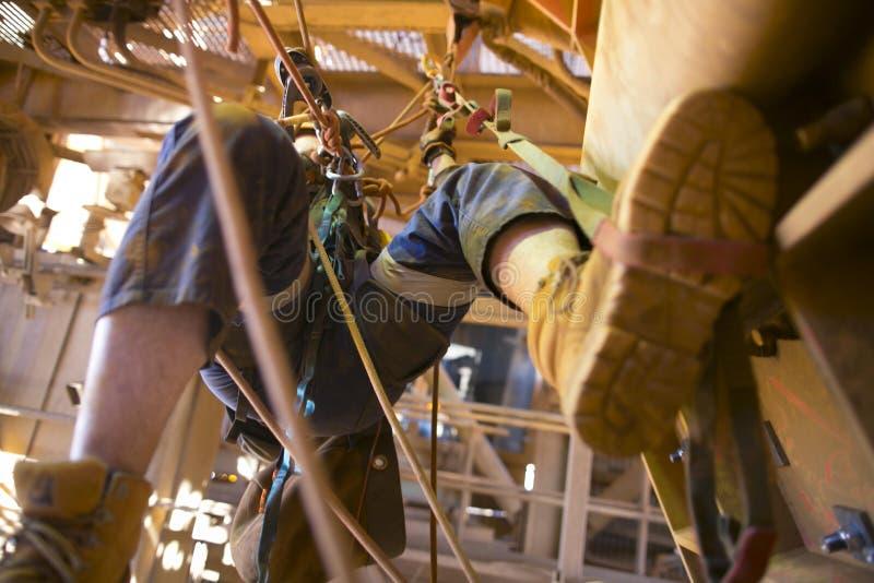 Imagem obscura do mineiro do acesso da corda que trabalha no hangin da altura em uma ascensão de começo de duas cordas usando o l fotografia de stock
