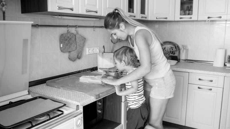 Imagem preto e branco da m?e nova que ensina seus 3 cookies de cozimento e de cozimento anos do filho idoso da crian?a na cozinha imagem de stock