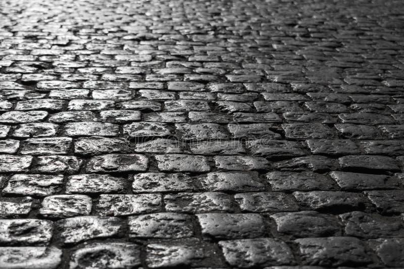 Imagem preto e branco de um close-up de uma estrada velha com uma textura da pedra sol-embebida no por do sol fotografia de stock