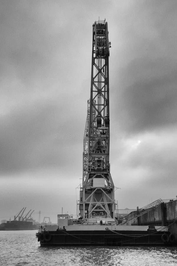 Imagem preto e branco de um guindaste histórico do vagabundo no porto de Hamburgo com as nuvens dramáticas no fundo fotografia de stock royalty free