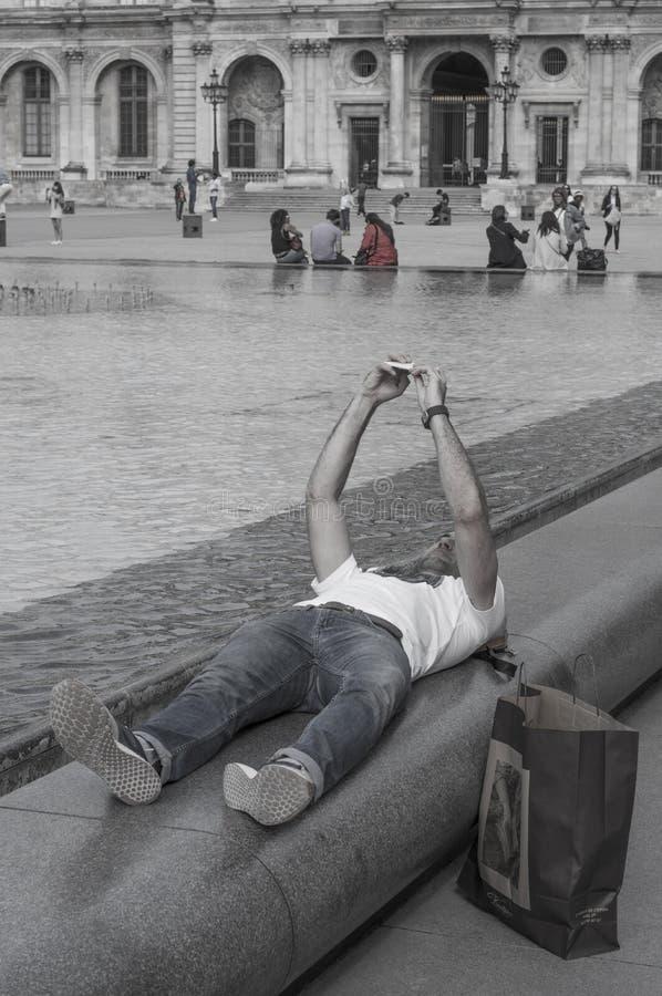 Imagem preto e branco de um homem novo que toma um selfie que encontra-se para baixo por um lado da associação no quadrado do Lou foto de stock royalty free
