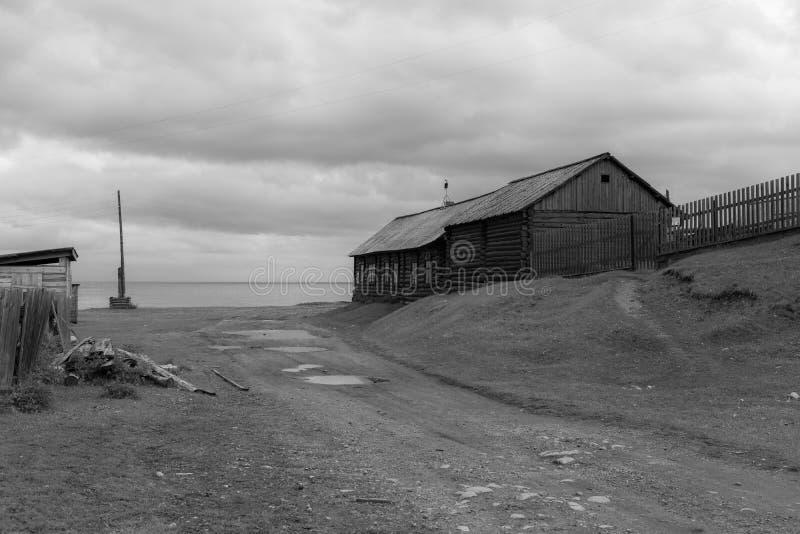Imagem a preto e branco de uma casa de madeira na beira do lago Baikal, na aldeia de Big Cats imagens de stock royalty free