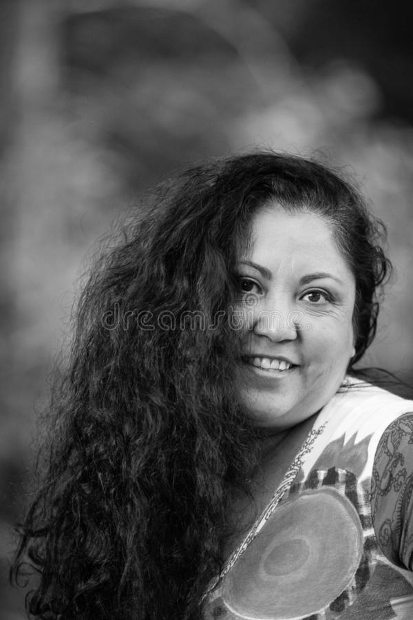 Imagem preto e branco de uma mulher mexicana de sorriso bonita com cabelo preto longo imagens de stock royalty free