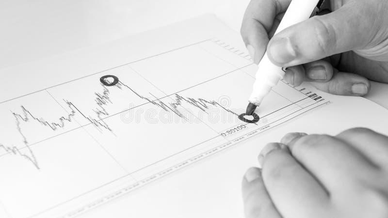 Imagem preto e branco do analista financeiro que tira o gráfico financeiro com marcador fotografia de stock