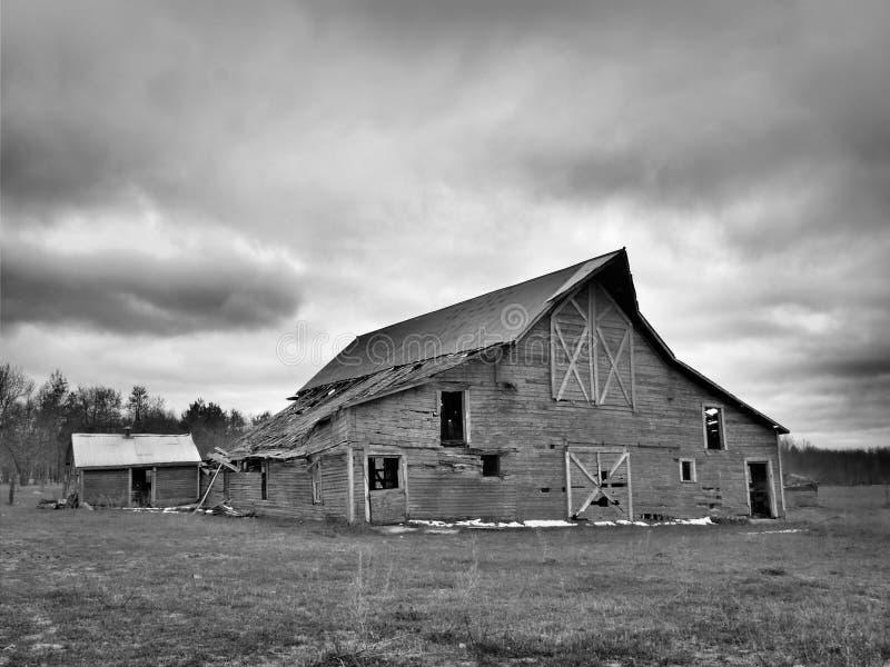 Imagem preto e branco do celeiro dilapidado abandonado aborrecido da exploração agrícola em Minnesota do norte foto de stock royalty free