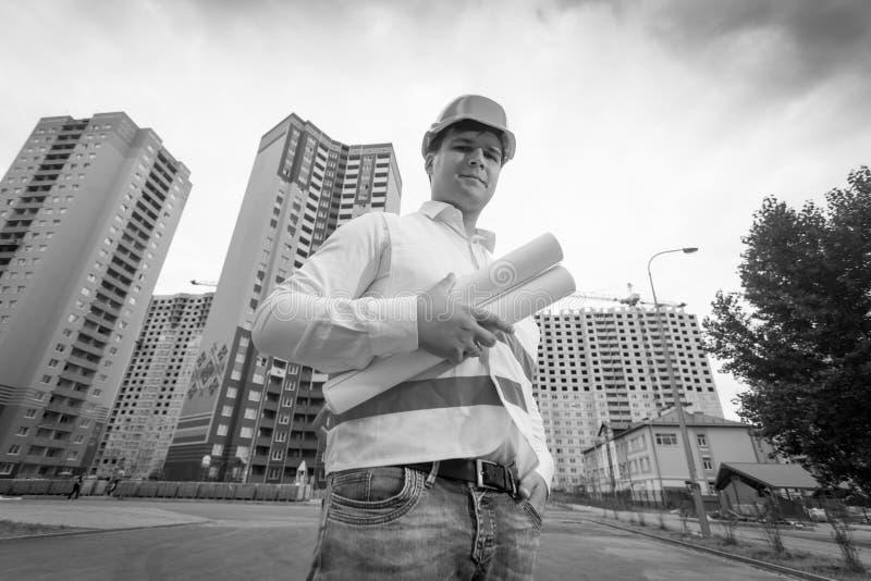 Imagem preto e branco do coordenador de construção masculino de sorriso no capacete de segurança imagens de stock