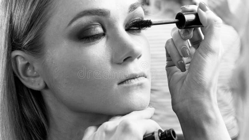 Imagem preto e branco do maquilhador profissional que aplica o rímel fotografia de stock royalty free