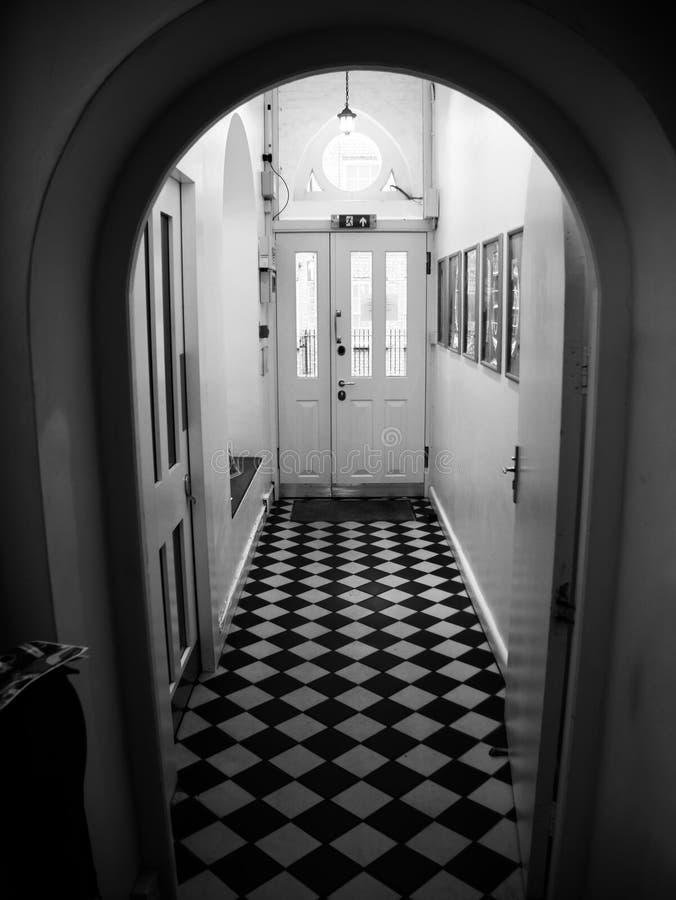 Imagem preto e branco um salão/corredor com o assoalho de mármore quadriculado fotos de stock