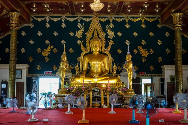 Imagem principal de buddha em shinning a cor dourada que senta-se no salão principal decorativo com a imagem da monge do apóstolo foto de stock