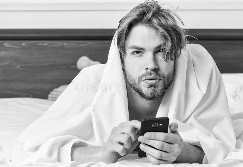 Imagem que mostra o homem novo que estica na cama P?s do homem que dormem na cama confort?vel Acorde a manh? fotografia de stock