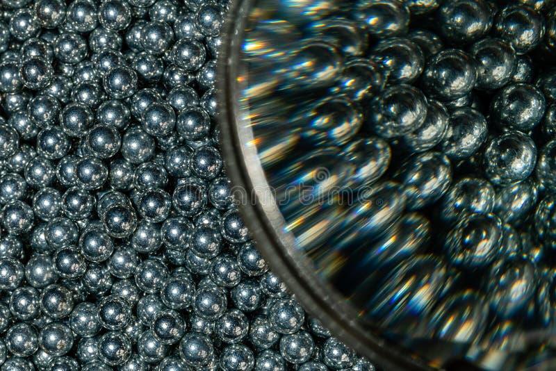 Imagem rachada da metade dos rolamentos de esferas de 3/16 de polegada no tamanho macro e da metade através de uma lupa no mesmo  fotos de stock