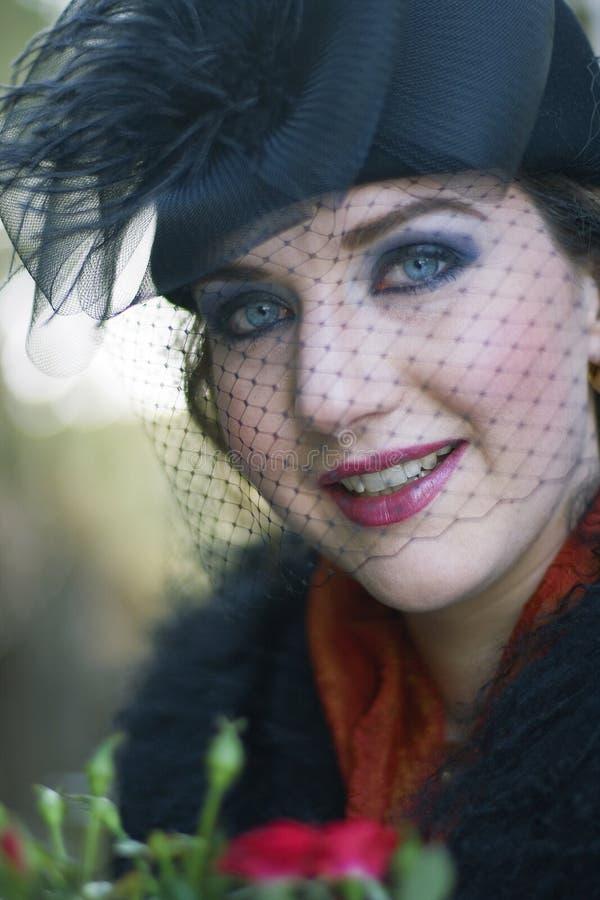 Imagem retro de uma mulher que desgasta um chapéu negro com VE foto de stock