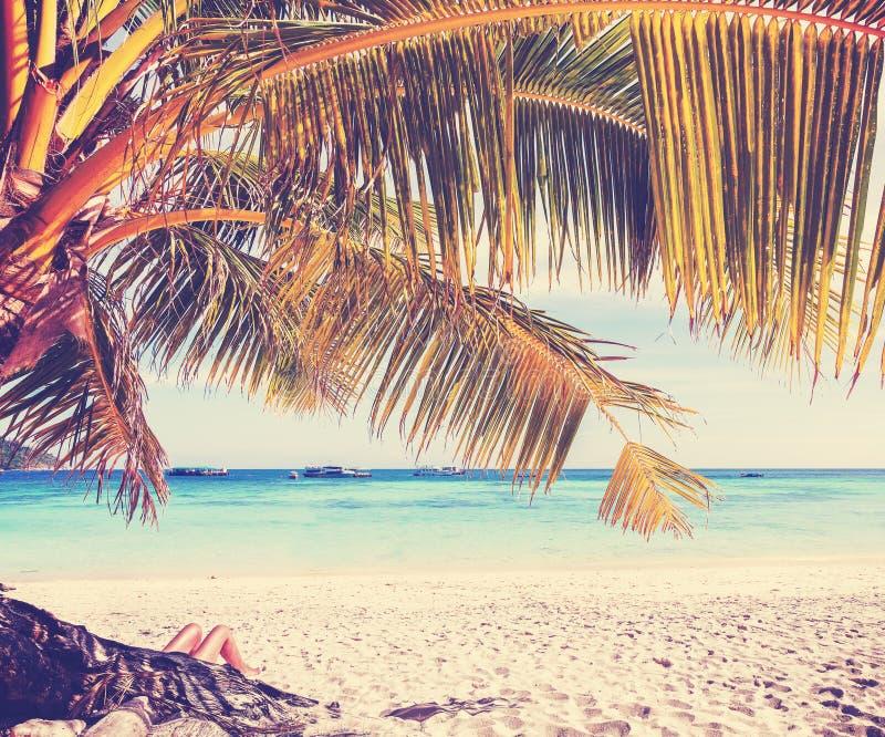 Imagem retro do estilo dos pés da mulher na praia tropical fotografia de stock