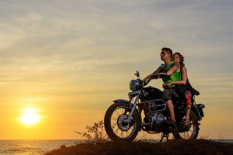 Imagem rom?ntica com um par motociclistas ? moda bonitos no por do sol Indivíduo considerável com tatoo e mulher 'sexy' nova fotografia de stock