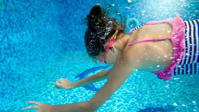 Imagem subaqu?tica do close up de 10 anos de nata??o e mergulho velhos da menina na piscina imagem de stock royalty free