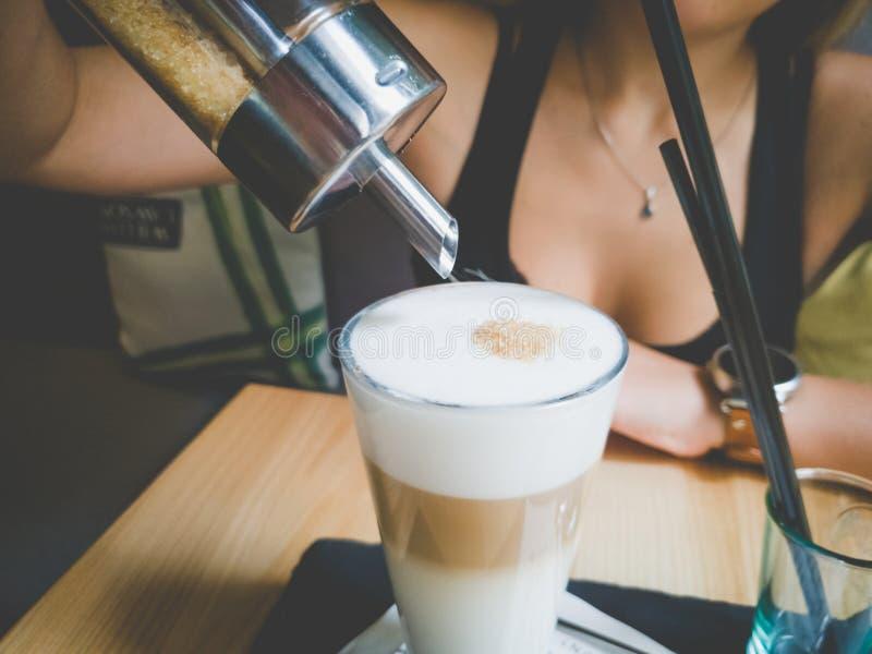 Imagem tonificada close up da jovem mulher bonita que senta-se no café e no açúcar de derramamento no café foto de stock royalty free