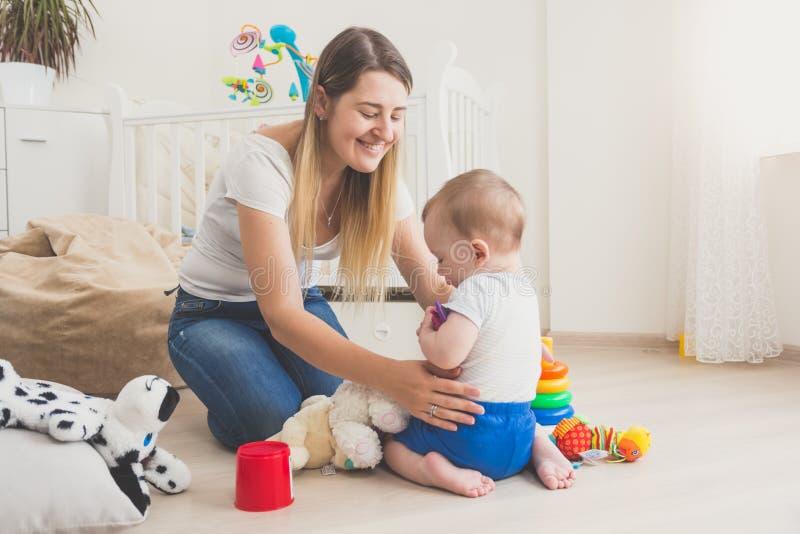 Imagem tonificada da mãe que joga com seu bebê em casa fotografia de stock royalty free