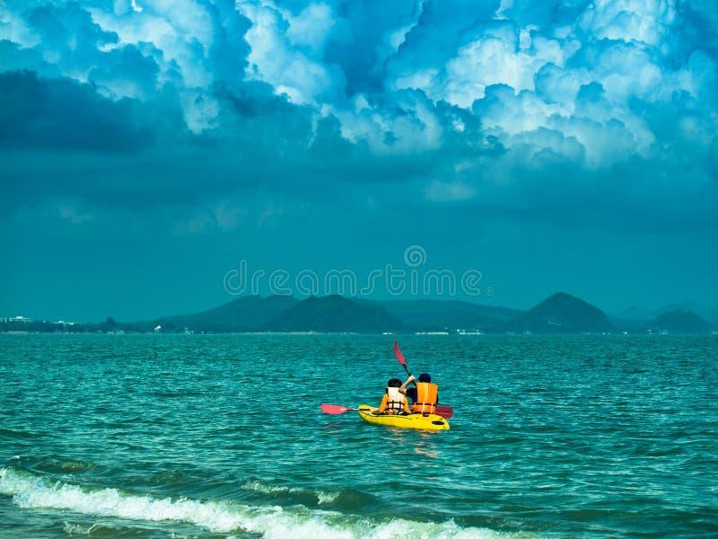 A imagem tonificada de um caiaque amarelo com dois turistas navega no mar no fundo do céu dramático foto de stock royalty free