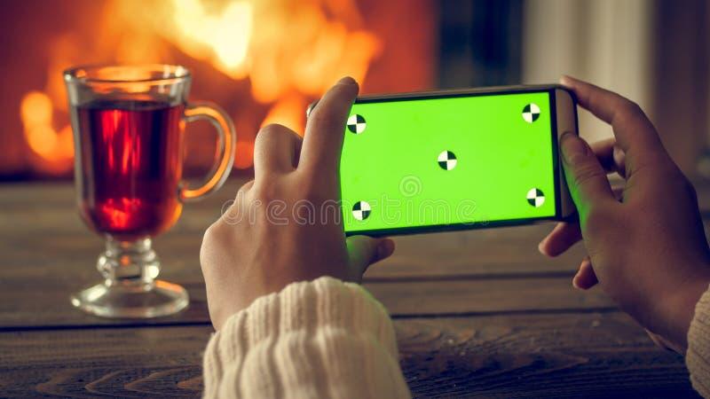 Imagem tonificada do close up das mãos fêmeas que fazem a foto no smartphone do chá e em chaminé ardente na noite Tela verde vazi imagens de stock royalty free