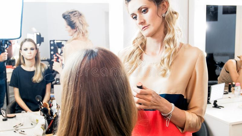 Imagem tonificada do maquilhador profissional que trabalha com modelo no estúdio da beleza fotografia de stock royalty free