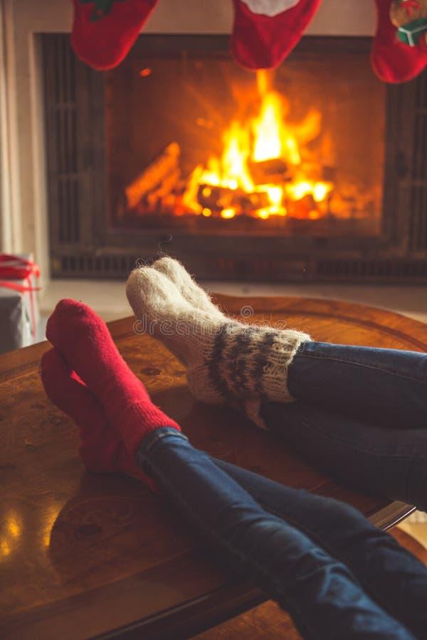 Imagem tonificada dos pares nas peúgas de lã que relaxam em firepl ardente imagem de stock royalty free