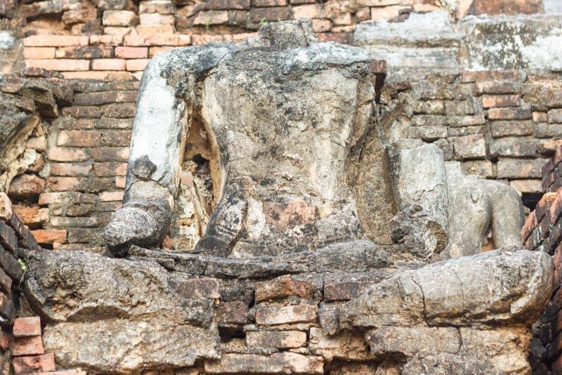 A imagem velha de buddha no cimento com ruínas e o Sukhothai antigo Tailândia foto de stock