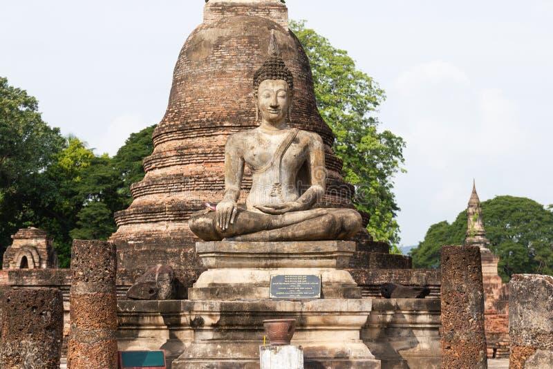 A imagem velha de buddha no cimento com ruínas e o Sukhothai antigo Tailândia fotografia de stock