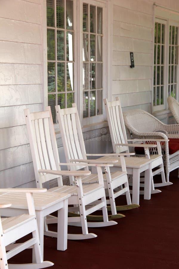 Imagem vertical da cadeira de balanço branca no patamar do país imagens de stock