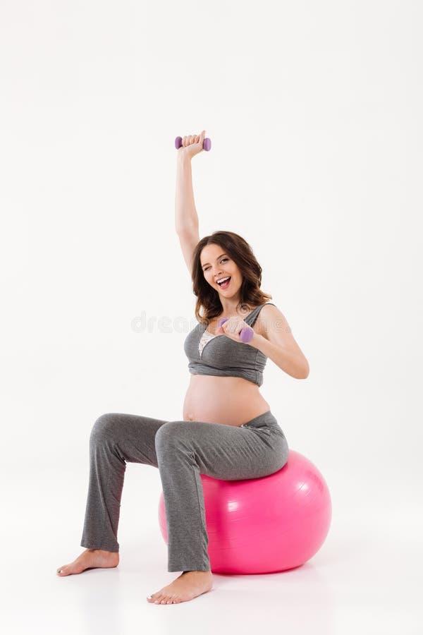 Imagem vertical da mulher gravida de sorriso que senta-se no fitball imagem de stock royalty free