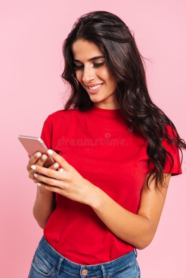 Imagem vertical da mulher moreno alegre que usa seu smartphone fotografia de stock