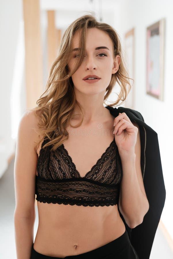 Imagem vertical da mulher 'sexy' no sutiã que guarda o revestimento imagem de stock