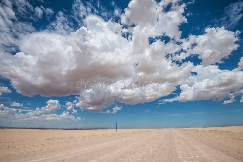 Imagem vibrante da estrada do deserto e do céu nebuloso azul foto de stock