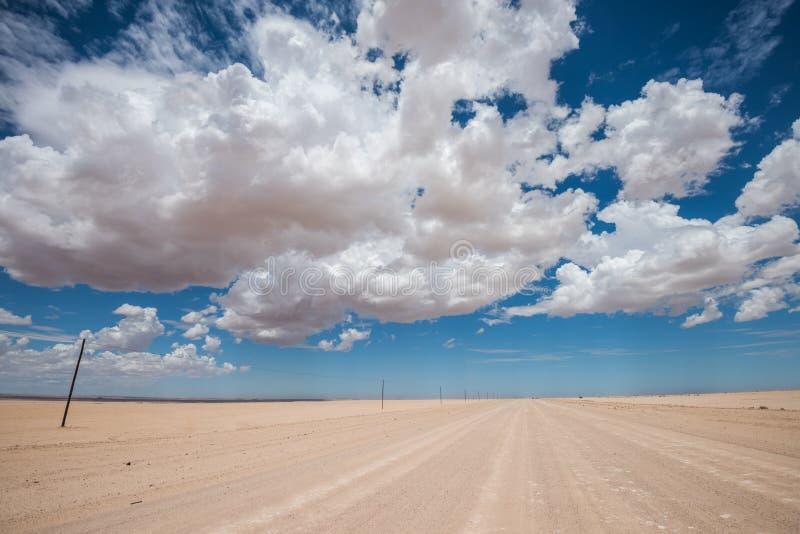 Imagem vibrante da estrada do deserto e do céu nebuloso azul foto de stock royalty free
