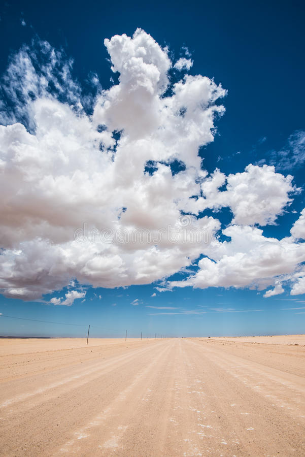 Imagem vibrante da estrada do deserto e do céu nebuloso azul fotografia de stock