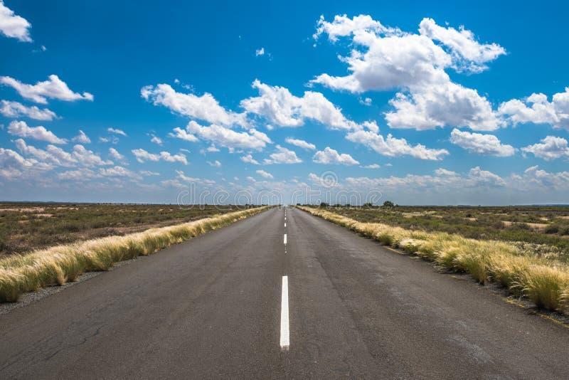 Imagem vibrante da estrada e do céu nebuloso azul foto de stock