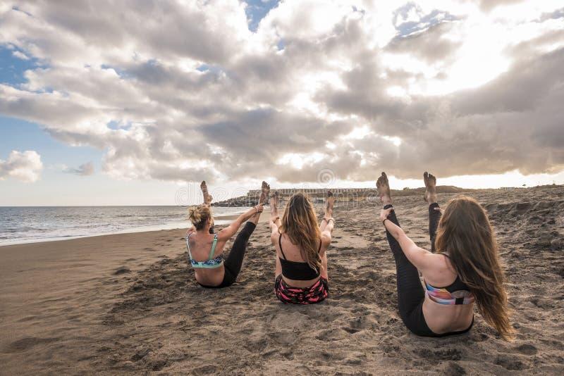 Imagen épica con las mujeres agradables jovenes que hacen ejercicios de la aptitud del entrenamiento y de los pilates en la playa fotografía de archivo libre de regalías