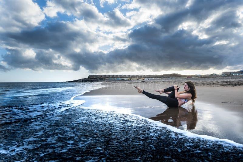 Imagen ?pica del estilo de los colores azules con la morenita bonita que hace actividad del deporte y de los pilates en la playa  foto de archivo