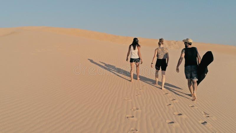 imagen aérea de la gente joven que camina para arriba en una duna de arena al pico en un ambiente hermoso del desierto fotos de archivo libres de regalías