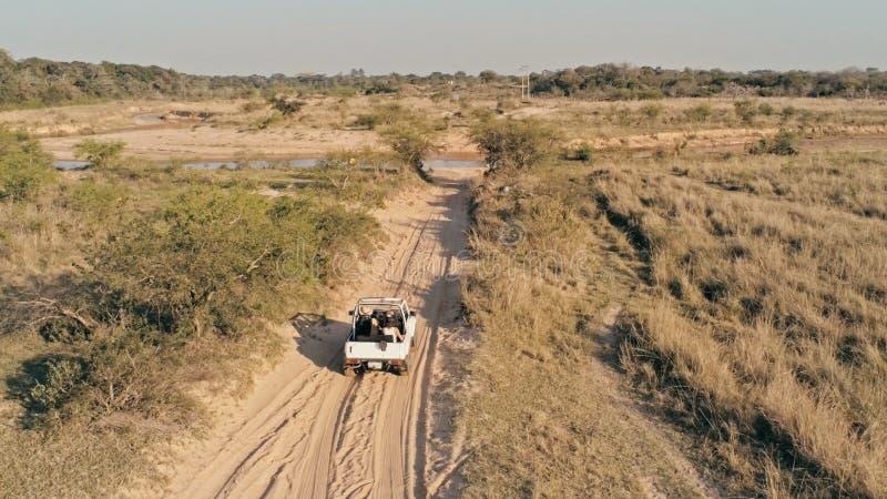 imagen aérea de un paisaje de la estepa del desierto con un coche 4x4 que se acerca a una pequeña corriente del río foto de archivo libre de regalías