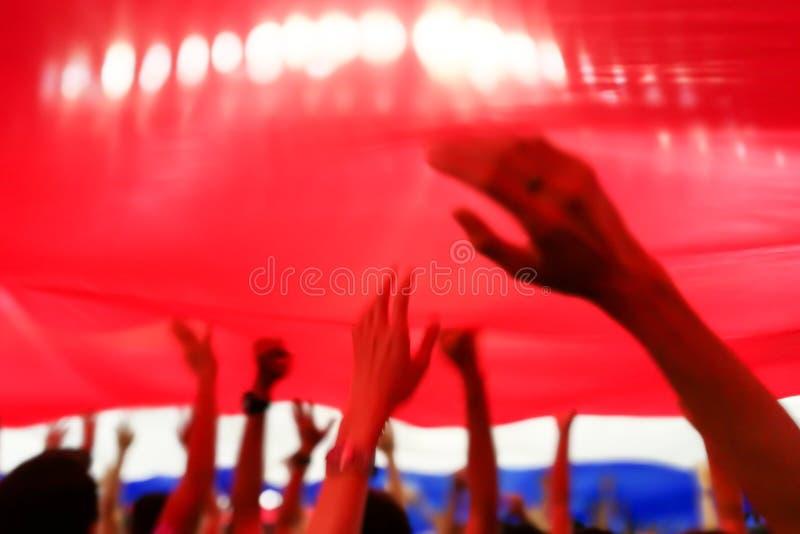 Imagen abstracta borrosa de la alegría del fútbol o del fútbol de la fan debajo de la bandera de Tailandia con la mano y la cabez imagenes de archivo