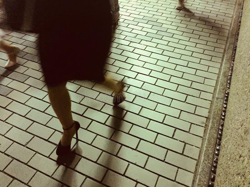 Imagen abstracta de las mujeres que caminan en un pavimento de piedra imágenes de archivo libres de regalías