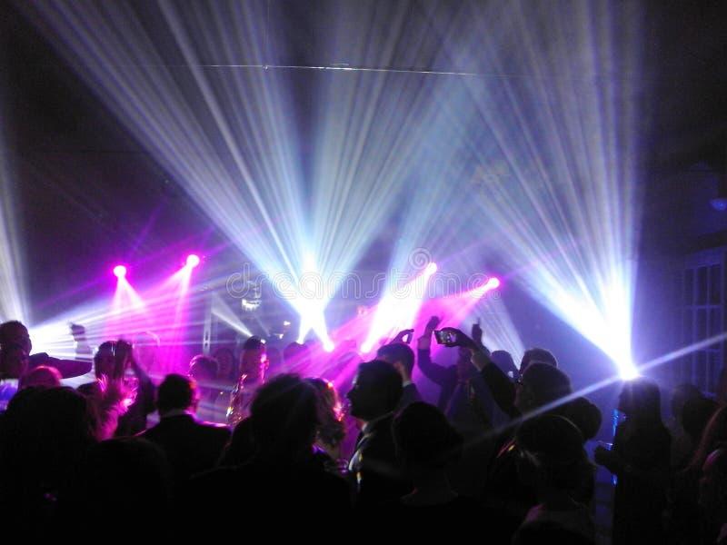 Imagen abstracta de las siluetas de la gente debajo de proyectores y de las luces de neón en un partido fotos de archivo libres de regalías