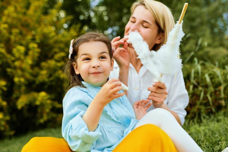 Imagen al aire libre de la madre feliz que come el caramelo de algodón con su hija que se sienta en la hierba en el parque D?a de imagen de archivo