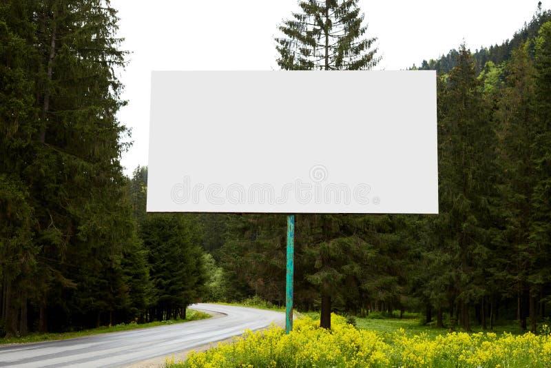 Imagen al aire libre de la situación enorme en blanco de la cartelera cerca del camino en manera a las montañas, teniendo muchos  fotografía de archivo