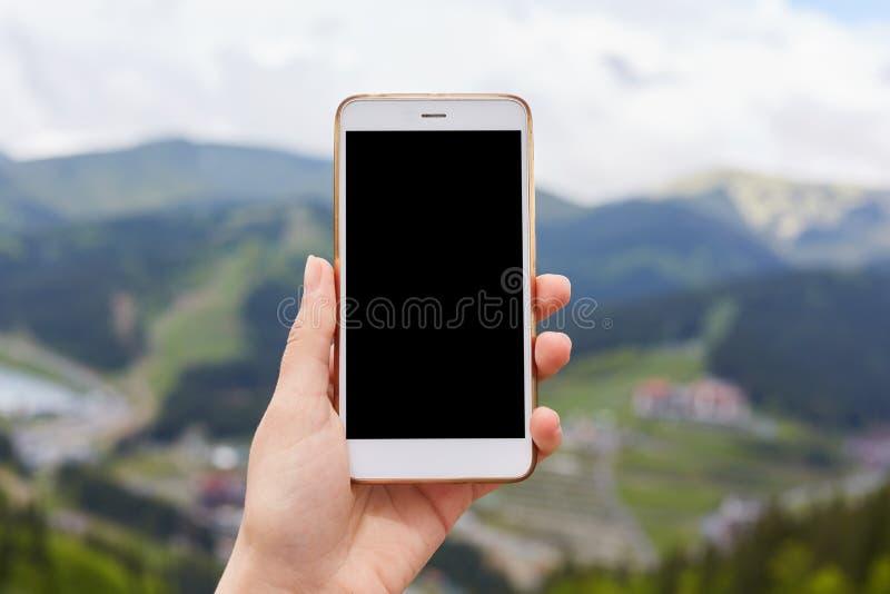 Imagen al aire libre de una mano que sostiene y que muestra el smartphone blanco con la pantalla de escritorio negra del espacio  imágenes de archivo libres de regalías